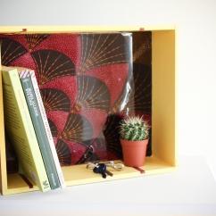 Mensola realizzata con una scatola di vini e decorata con inserti di tessuto africano e resina